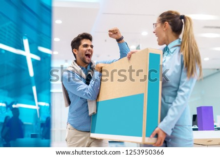 Happy multicultural couple dressed elegant holding box with new television in it. Tech store interior.