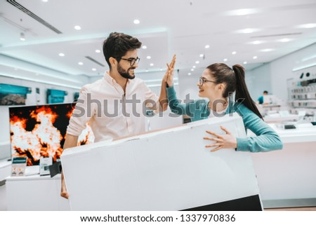 Happy multicultural couple holding new smart tv in box and giving high five while standing at tech store.
