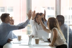 Happy multicultural executive team people give high five, diverse motivated office employees group engaged in teambuilding spirit promise trust integrity celebrate shared business success win concept