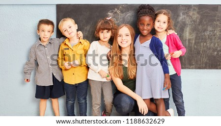 Happy multicultural group of kids with teacher in elementary school in front of a blackboard #1188632629