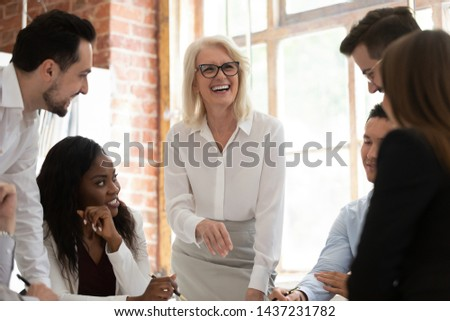 Happy multicultural office young employees with old mentor leader coach laughing working together gather in boardroom, diverse corporate business team having fun engaged in teamwork at group meeting