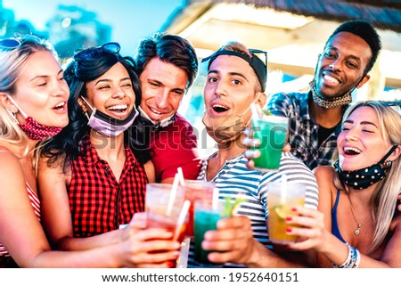 Happy multicultural people toasting at night bar with open face masks - New normal life style concept with milenial friends having fun together - Shallow depth of field with focus on middle guy Foto stock ©