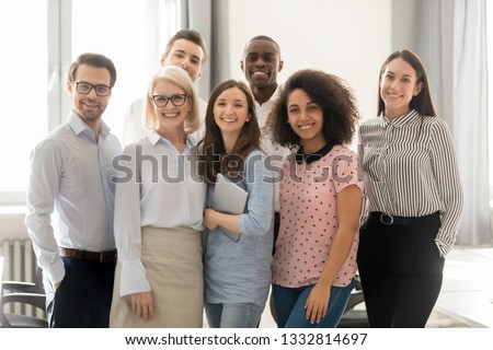 Happy multicultural work team employees group looking at camera posing in office, smiling multi-ethnic company staff workers, workforce members, business people managers standing together, portrait