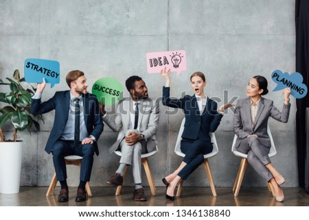happy multiethnic businesspeople holding speech bubbles with idea, success, planning and strategy lettering while sitting in waiting hall