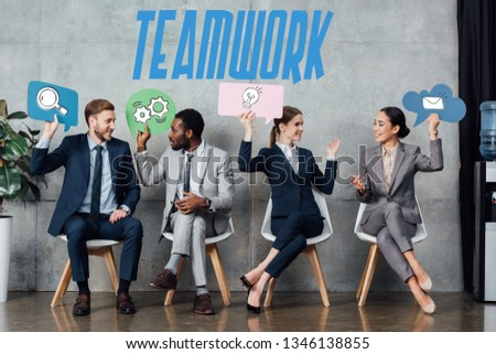 happy multiethnic businesspeople holding speech bubbles with teamwork icons while sitting in waiting hall