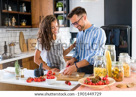 Happy multiethnic couple cooking homemade tomato and basil pasta. Cooking at home