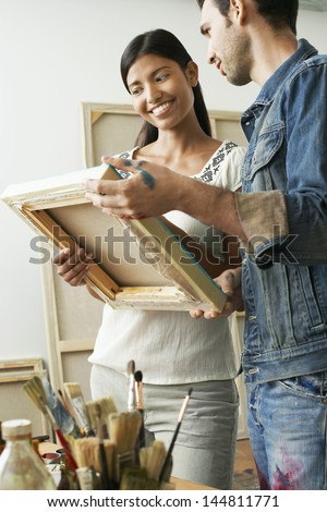Happy multiethnic couple looking at canvases in artist studio