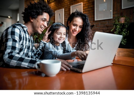 Happy multiethnic family having fun while using laptop together at restaurant Foto stock ©