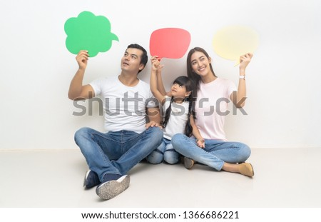 Happy multiethnic family holding blank colorful speech bubbles and looking up at home.