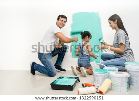 Happy multiethnic family renovating their new home.Father sitting near daughter, smiling painting with a roller and looking at camera.