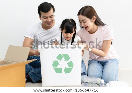 Happy multiethnic family siblings having funsorting segregating household waste at home.Lifestyle - ecological education and awareness concept
