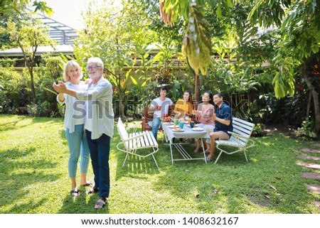 Happy multiethnic family sitting at a breakfast table in backyard outdoor on sunny day with smiling face while caucasian dad and caucasian mom dancing. #1408632167