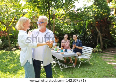 Happy multiethnic family sitting at a breakfast table in backyard outdoor on sunny day with smiling face while caucasian dad and caucasian mom dancing. #1421095919
