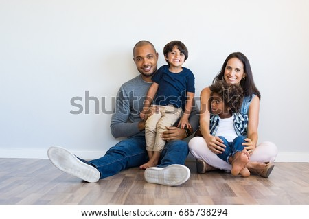 Happy multiethnic family sitting on floor with children. Smiling couple sitting with two sons and looking at camera. Mother and black father with their children leaning on wall with copy space. Foto d'archivio ©
