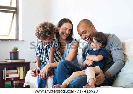 Happy multiethnic family sitting on sofa laughing together. Cheerful parents playing with their sons at home. Black father tickles his little boy while the mother and the brother smile. #717416929