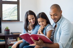 Happy multiethnic family sitting on sofa together looking at daughter's drawing book. Black father reading the homework on exercise book of his cute kid. Parents feeling proud on progress of daughter.