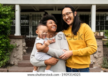 Happy multiethnic family standing in front of the house during covid19 lockdown