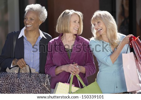 Happy multiethnic female friends with shopping bags - stock photo
