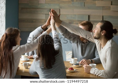 Happy multiethnic friends meeting in café giving high five showing support and unity, excited young people sitting in coffeeshop enjoying time together raising hands joining, promising friendship