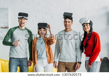 happy multiethnic friends putting on virtual reality headsets, one man showing thumb up