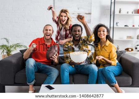 Happy multiethnic friends sitting on couch, watching match and holding bowl of popcorn