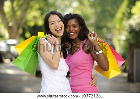 happy multiethnic friends with shopping bags