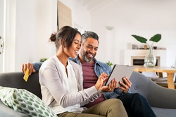 Happy multiethnic mature couple using digital tablet for online payment with credit card. Latin wife showing something to buy on digital tablet to her indian husband. Middle eastern couple relaxing.