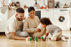 Happy multiethnic parents and boy playing with toys on floor in cozy kitchen at home