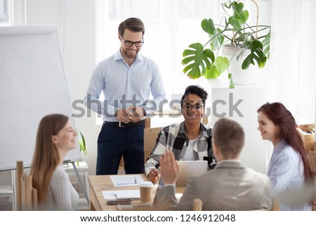 Happy multiethnic team brainstorming in loft office discussing or negotiating over ideas, male leader or speaker present on flipchart, business mentor or coach give presentation to diverse workers