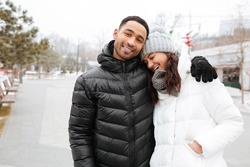 Happy multiethnic young couple hugging and laughing in winter park