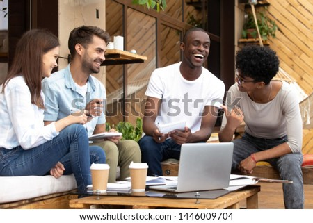 Happy multiethnic young people meet in coffee place work using laptop making notes, smiling diverse millennial friends gather in café studying together with computer have fun laughing sharing ideas