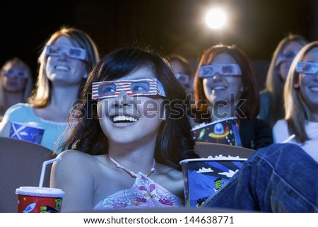 Happy multiethnic young women watching a 3-D movie in the theatre
