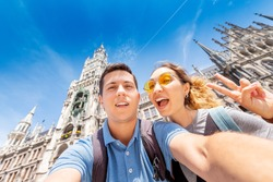 happy multinational couple in love hugs and takes a selfie photo on the background of The city hall tower in Munich. Honeymoon trip to Germany