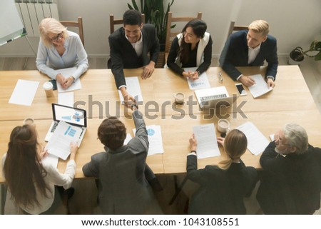 Happy multiracial businessmen shake hands at diverse group meeting, black and white partners handshaking after successful teamwork or team negotiations sitting at conference table, top view overhead