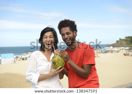 Happy multiracial couple enjoying vacation drinking coconut water on the boardwalk of Ipanema, Rio de Janeiro.