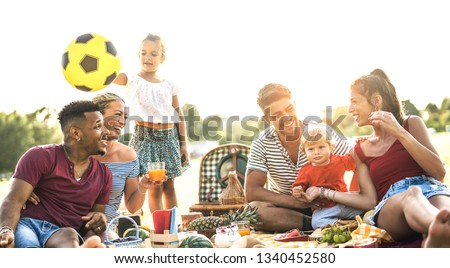 Happy multiracial families having fun together with kids at pic nic barbecue party - Multicultural joy and love concept with mixed race people playing with children at park - Warm contrasted filter