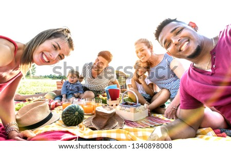 Happy multiracial families taking selfie at pic nic garden party - Multicultural joy and love concept with mixed race people having fun together at sunset picnic barbecue - Warm vivid sunshine filter