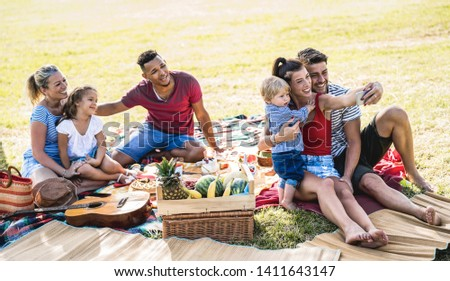 Happy multiracial families taking selfie at pic nic garden party - Multicultural joy and love concept with mixed race people having fun together picnic barbecue before sunset - Warm bright filter