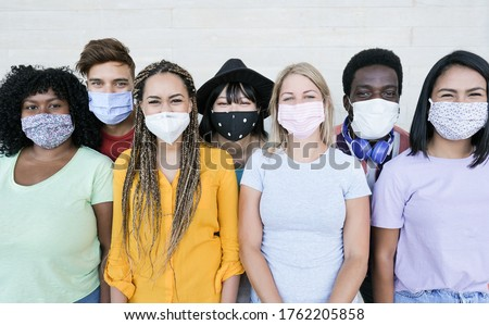 Happy multiracial friends laughing and wearing protective face mask - Group of young peoples having fun together - Concept of lifestyle, health care and the new normality Сток-фото ©