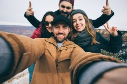 Happy multiracial friends show thumbs up and make selfie photo on travel hiking at Grand Canyon viewpoint in winter, Arizona, USA