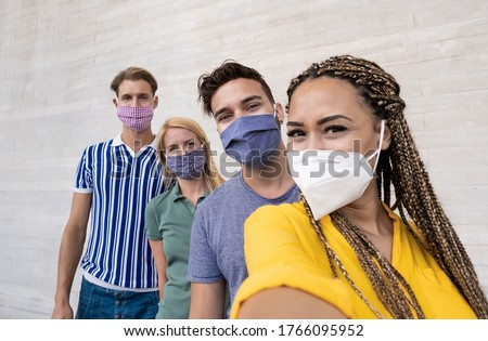 Happy multiracial friends taking a selfie and wearing protective face masks - Concept of health care and the new normality - Focus on the men on the right