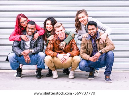 Happy multiracial group of best friends portrait on grey wall background at winter time - Different culture teamwork students huddled together posing photo outdoors for integration and peace concept