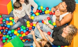 Happy multiracial mom and dad playing with daughter inside ball pit swimming pool with soap bubble blower - Multicultural family concept with happy children having fun with parents at kid toyroom