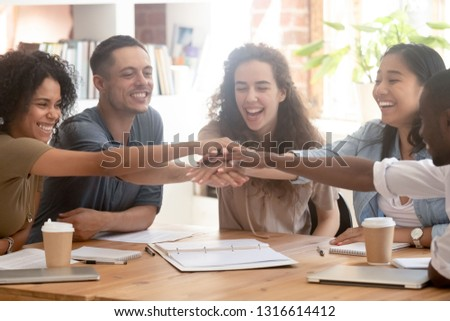 Happy multiracial office business people colleagues employees engaged in teambuilding stacking hands motivated by corporate success, team support unity power, help in teamwork collaboration concept