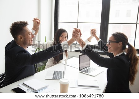 Happy multiracial team holding hands promising unity and engagement, teambuilding concept, excited diverse colleagues celebrating victory, great teamwork result, business success, good relations