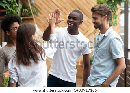 Happy multiracial young people hang out outdoors together give high five greeting, smiling diverse multiethnic millennial friends join hands celebrating shared win or gather for meeting