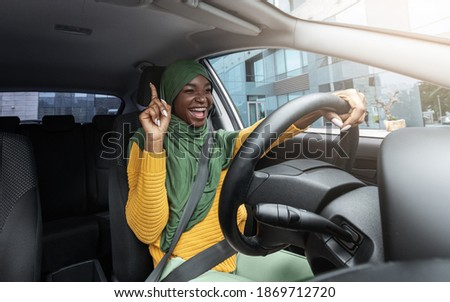 Happy muslim black female driver in hijab singing and dancing while driving car in city, cheerful islamic lady in headscarf having fun and enjoying road trip with her new vehicle, free space Stock fotó ©