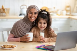 Happy Muslim Mom And Daughter Having Snacks And Drinks In Kitchen, Happy Islamic Lady In Hijab Enjoying Coffee And Her Cute Little Child Drinking Milk. Cheerful Family Smiling At Camera, Free Space