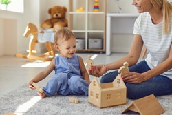 Happy nanny and child playing game with wood blocks together. Babysitter looking after little kid. Cute toddler boy and mother sitting on warm floor in modern nursery room building toy house