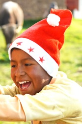 Happy native american boy wearing typical red Santa Claus hat.